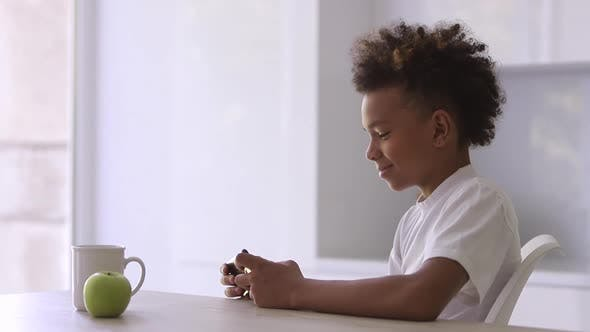 Cheerful African American Boy is Using Electronic Gadget at Table in Apartment Room Spbi