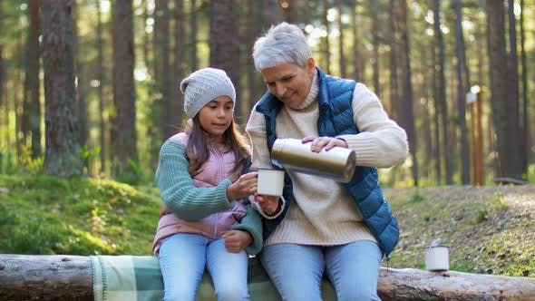 Thumbnail for Grandma with Granddaughter Drinking Tea in Forest