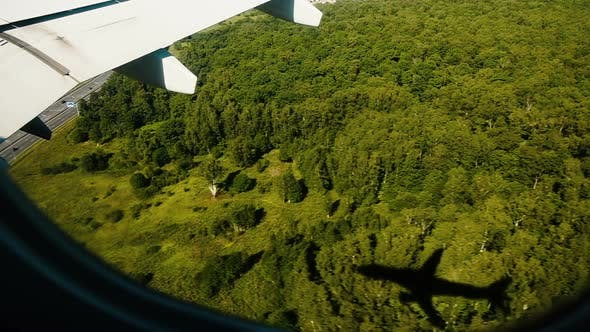 Thumbnail for Airplane Shadow From the Porthole Window Flies Over the Forest on the Landing