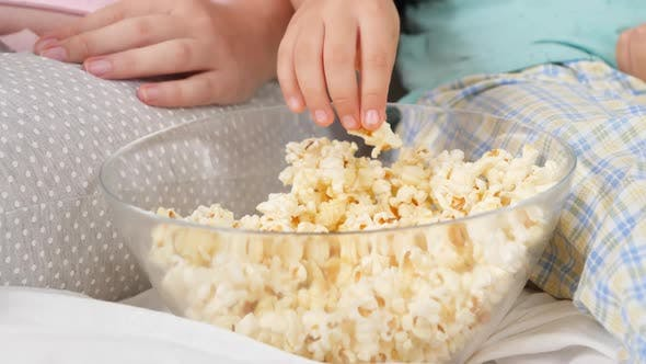 Thumbnail for CLoseup of Family Eating Popcorn From Big Bowl