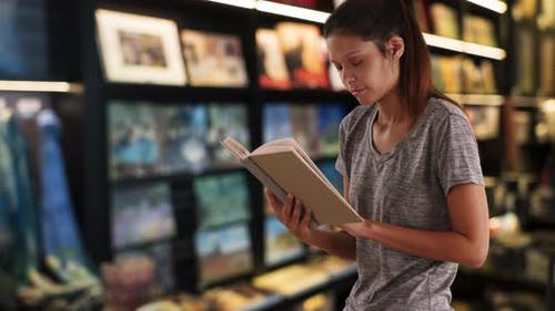 Beautiful young woman reading in bookstore