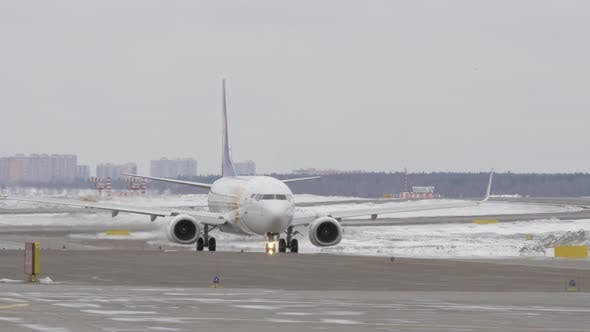 Boeing 737-800 of Mongolian Airlines Taxiing on Runway, Winter View