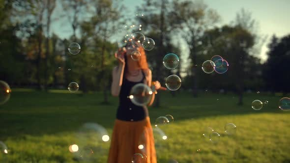 Thumbnail for Beautiful Young Redhair Girl Blowing Soap Bubbles Outdoors. Sunrise