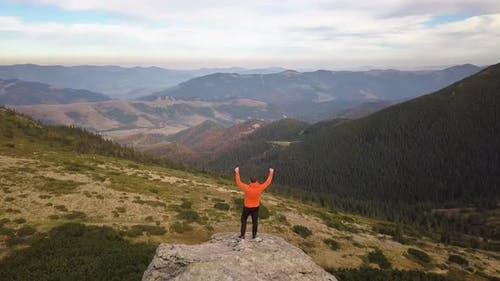 Aerial view of a hiker man raising his hands on a big rock in mountains.
