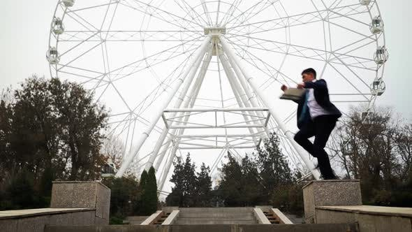 Successful Man in Business Suit Jumps Over an Obstacle Background Ferris Wheel