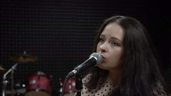Professional female singer sings emotional song in recording studio. Music concept