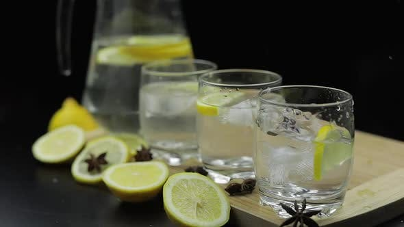 Thumbnail for Add Ice Cubes To Lemon Juice in Glass with Lemon Slices. Alcoholic Cocktail
