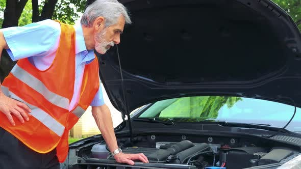 Thumbnail for Senior Man Wears Warning Vest, Controls Engine of the Car and He Doesn't Know What To Do