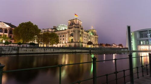 Sunrise hyper lapse of the Reichstag government building in central Berlin, spree river water front