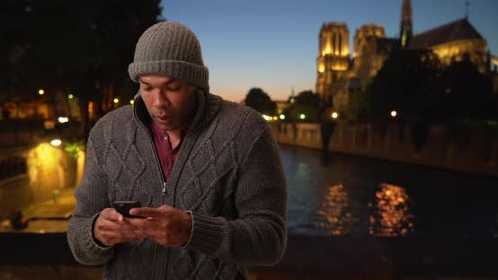 Thumbnail for African man in Paris, France trying to reach friend on phone on chilly evening