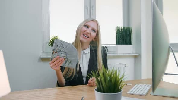Smiling Business Woman Holding Wad of Cash. Beautiful Happy Blond Female Sitting in Office at