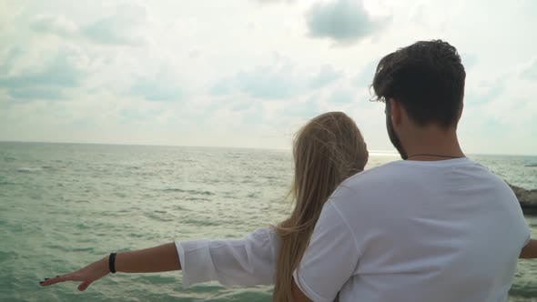 Cover Image for Young Couple in White Dress Standing at the Beach Close Up. Man Cuddling Woman From Behind, Lady