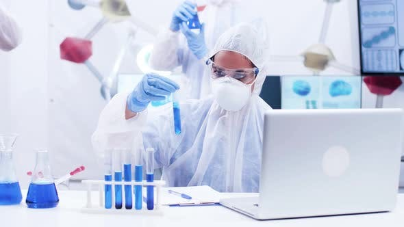 Cover Image for Female Scientis Holding a Test Tube with Smoking Blue Fluid and Writing Formula