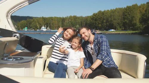 Family with Daughter Vacation Together on Sailboat in Lake