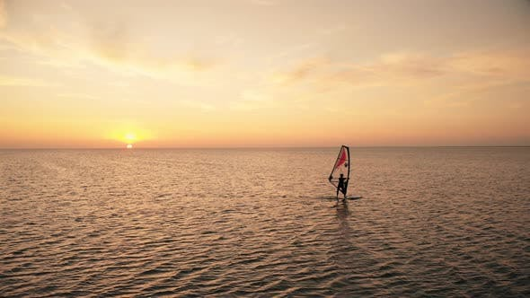 Distant Person Sails Windsurf Board on Ocean at Sunset