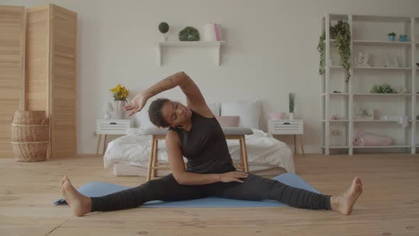 Sporty Woman Doing Side Bending Exercise at Home