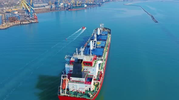 Thumbnail for Aerial View. Large Cargo Ship Enters the Port City with Port Cranes.