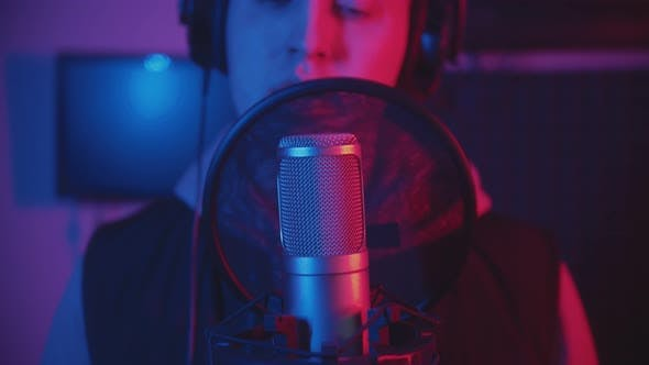 Thumbnail for A Man Rapping Through the Pop-filter in the Microphone - Recording His Track in the Studio