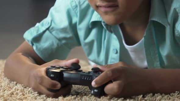 Cover Image for Little Child Lying on Floor with Play Station Control Playing Video Games, Anger
