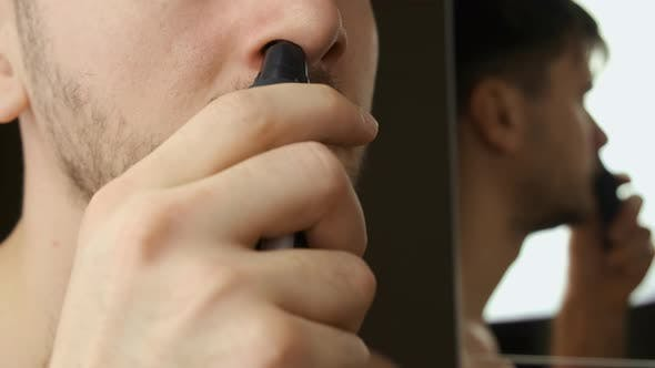 Man Uses Electric Power Trimmer To Trim Hair in the Nose. Daily Morning Routine.