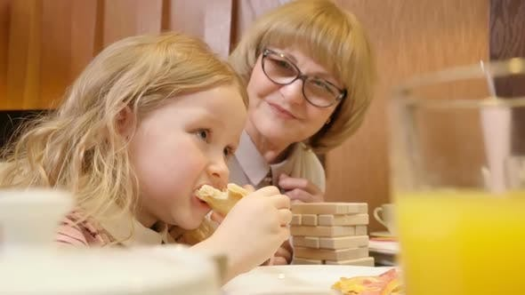 Thumbnail for Cute Girl Eating Pizza at Cafe with Grandma