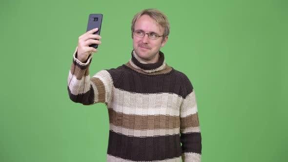 Cover Image for Studio Shot of Happy Handsome Man Taking Selfie