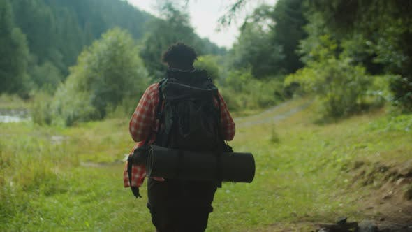 Handsome African American Man Hiker with Backpack Trekking Near Mountain River
