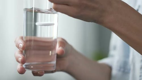 Woman Holding Glass of Water, Putting Tablet of Aspirin Into It, Painkiller