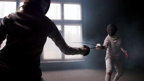 Cover Image for Two Young Women Having Training in a Fencing Duel in the Smoky Studio