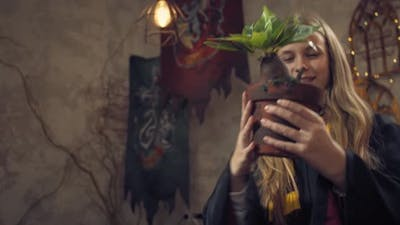Student of the Wizard School is Holding a Flower Pot with Mandragora Root