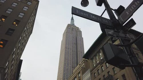 Low Angle Pan Shot Midtown Manhattan Street Signs and the Empire State Building