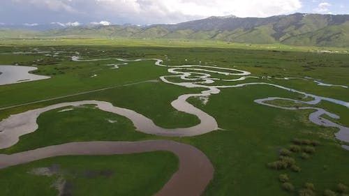 Winding river flowing through green valley in Wyoming
