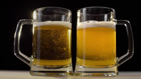 Thumbnail for Two Beer Glasses Are Poured with Foamy Golden Light Beer on Black Background, Beer with Friend