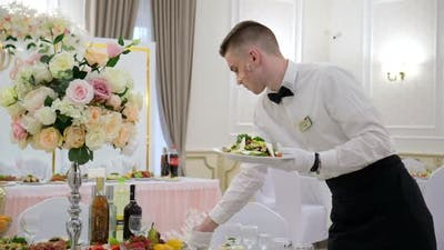 Young Waiter Serving Food in a Restaurant