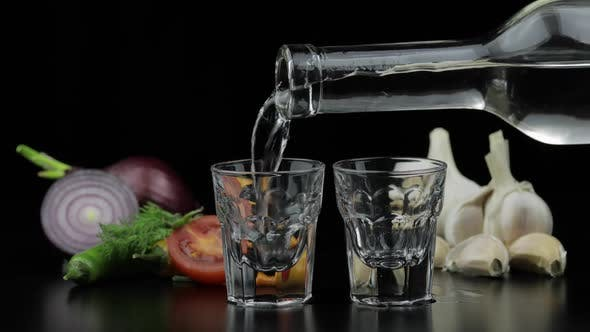 Pour Alcohol Vodka From a Bottle in Two Shot Glass. Background with Vegetables