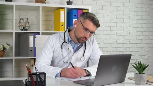 Doctor wears white medical coat in hospital office using laptop writes notebook