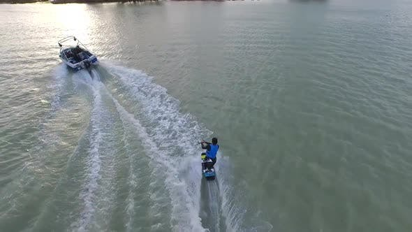 Thumbnail for Aerial shot of young man wake boarding behind a motorboat in a lake.