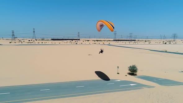 Thumbnail for Aerial view of a man using powered parachute at desert landscape, Dubai, U.A.E.
