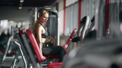 Beautiful Woman Doing Fitness Exercise on Sport Simulator in Gym Club
