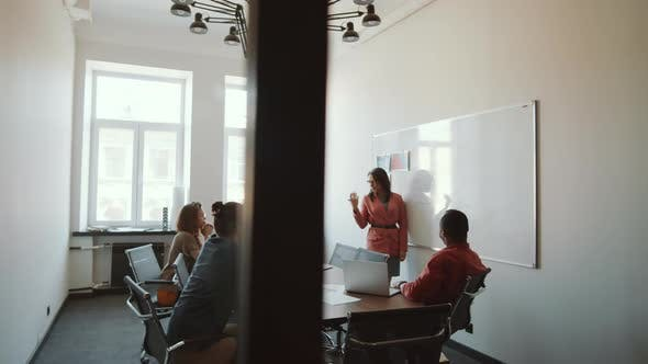 Thumbnail for Businesswoman Giving Presentation to Colleagues in Meeting Room