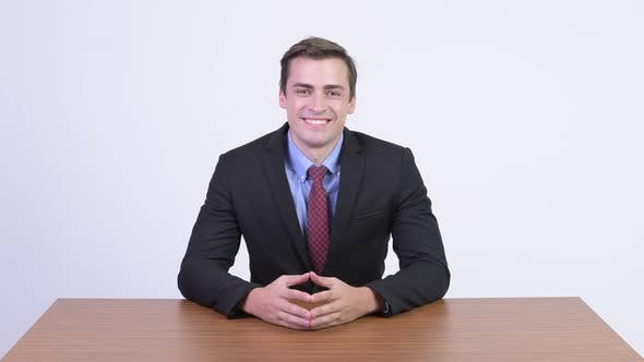 Thumbnail for Young Handsome Businessman Thinking Against Wooden Table