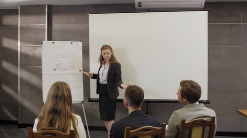 Female Coach Gives Corporate Presentation On Whiteboard
