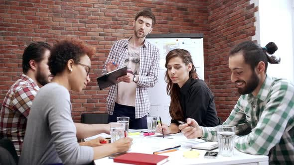 Team Lead Standing Next to Table with Teammates Coworkers Discuss Work Business Meeting of People in