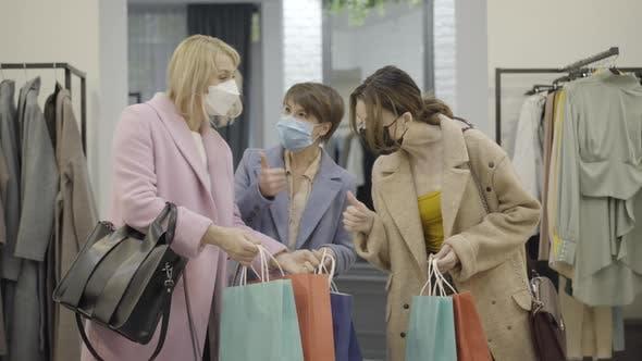 Thumbnail for Mittelaufnahme selbstbewusster junger Frauen in Covid-19-Gesichtsmasken mit Blick auf Einkäufe in Einkaufstaschen