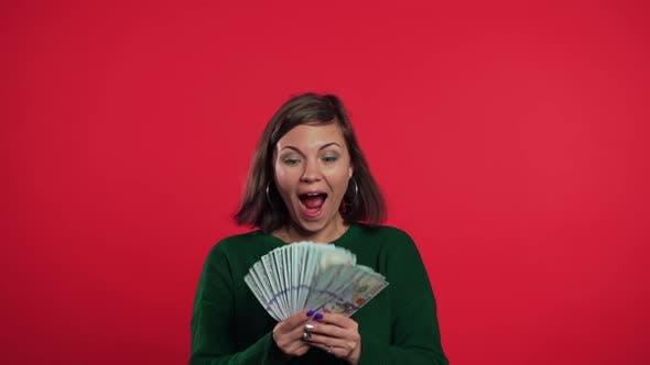 Thumbnail for Aufgeregtes Mädchen in grünem Pullover mit Geld - US-Dollars Banknoten
