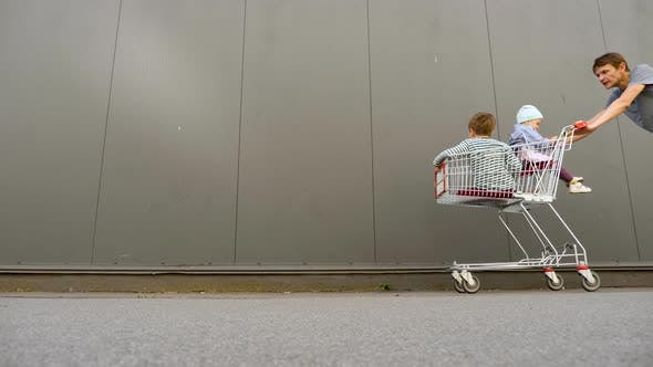 Thumbnail for Family with Two Children Going Shopping. Young Consumers in Shopping Cart. Family Having Fun Going