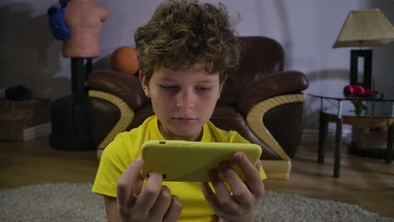 Thumbnail for Scared Face of Caucasian Boy Watching Movies on Smartphone Screen. Cute Child with Grey Eyes and
