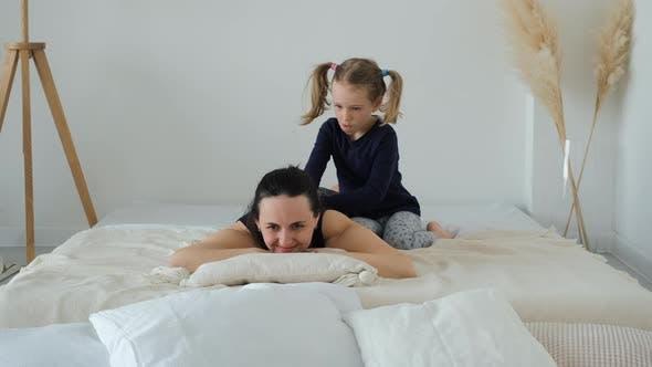 Kleines Mädchen, das Mutter zu Hause massiert