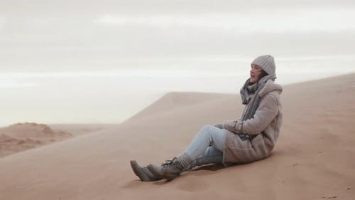 Happy Young Caucasian Female Tourist Posing, Sitting on Cold Sand Dune Beach Under Extreme Wind