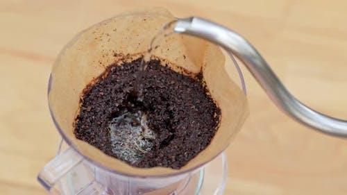 Barista gießt Wasser in den Filter mit Kaffee